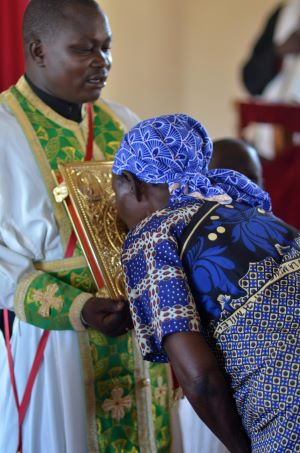 Kenyan priest holding the Gospel as the faithful venerate
